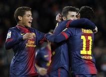David Villa consiguió el miércoles el gol número 301 en su carrera con los dos tantos anotados para el Barcelona en Copa del Rey, donde los culés se clasificaron para octavos de final tras derrotar al Alavés, de segunda B, por un marcador global de 6-1. En la imagen, Villa celebra un gol con sus compañeros Thiago Alcántara (D) y Jonathan Dos Santos el 28 de noviembre de 2012. REUTERS/Albert Gea