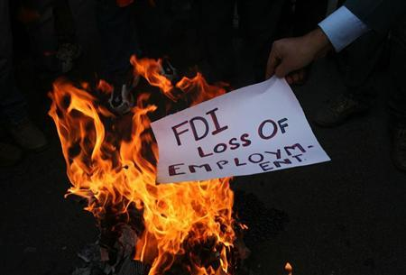 An activist of Shiv Sena, a Hindu hardline group, burns a pamphlet during a protest against Foreign Direct Investment (FDI) in retail sector, in Jammu November 30, 2011. REUTERS/Mukesh Gupta