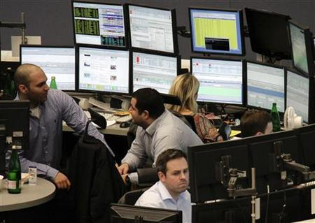 Traders are pictured at their desks at the Frankfurt stock exchange January 2, 2012. REUTERS/Remote/Pawel Kopczynski/Files