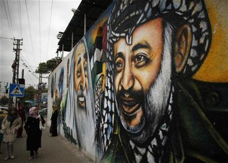 Palestinians walk next to a mural depicting late Palestinian leader Yasser Arafat (R) in Gaza City November 27, 2012. REUTERS/Suhaib Salem