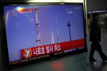A passenger walks past a TV screen broadcasting the news that the launch of Korea Space Launch Vehicle-1 (KSLV-1), or Naro, was cancelled due to a problem in the upper second-stage rocket, at a railway station in Seoul November 29, 2012. South Korea cancelled the launch of its first space rocket on Thursday after a glitch in the propulsion system halted the countdown just minutes before the scheduled lift-off. It was the second delay in South Korea's third attempt to put a satellite into orbit, after October's scheduled launch was also called off due to a glitch in the Russian-built booster. No new launch schedule has been determined. REUTERS/Kim Hong-Ji