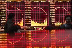 """Люди смотрят на электронное табло в брокерском доме в Шанхае 27 декабря 2010 года. Азиатские фондовые рынки, кроме Китая, выросли благодаря признакам прогресса в переговорах о """"бюджетном обрыве"""" в США. REUTERS/Aly Song"""
