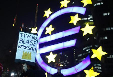 A woman holds a sign in front of the Euro currency sign next to the European Central Bank (ECB) headquarters during a demonstration against the Euro Finance Week in Frankfurt November 23, 2012. REUTERS/Lisi Niesner