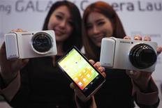 El gigante surcoreano de la electrónica Samsung Electronics apunta a sus rivales japoneses con una cámara digital accionada por Android que permite a los usuarios cargar rápidamente fotos de forma inalámbrica a las redes sociales. En la imagen, de 29 de noviembre, dos modelos posan con la Galaxy Camera de Samsung durante un evennto en Seúl. REUTERS/Kim Hong-Ji