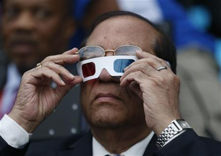 Acting Indian Olympic Association President Vijay Kumar Malhotra tries on his glasses as he sits in the stands before the opening ceremony of the London 2012 Olympic Games at the Olympic Stadium July 27, 2012. REUTERS/Suzanne Plunkett