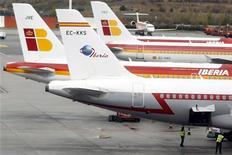 Los sindicatos de Iberia han convocado huelgas en seis días de diciembre para protestar contra del plan de reestructuración de la compañía que prevé el recorte de casi el 25 por ciento de su plantilla, dijo un portavoz de UGT, confirmando lo adelantado el miércoles por fuentes sindicales. En la imagen, empleados de Iberia bajo aviones de la compañía aparcados en el aeropuerto Madrid Barajas, el 9 de noviembre de 2012. REUTERS/Sergio Pérez