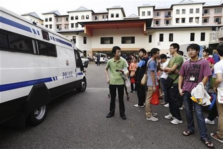 A police van reverses out of the premises of a dormitory as negotiations with striking bus drivers continue within the building in Singapore in this file photo taken November 26, 2012. REUTERS/Edgar Su