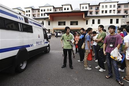 A police van reverses out of the premises of a dormitory as negotiations with striking bus drivers continue within the building in Singapore November 26, 2012. REUTERS/Edgar Su