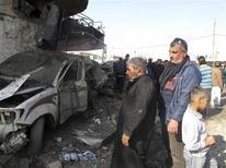Moradores de Hilla, a 100 quilômetros de Bagdá, observam local atingido por carro-bomba nesta quinta-feira, quando 28 pessoas morreram em atentados no país. 28/11/2012 REUTERS/Habib