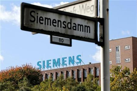 A street sign is pictured in front of a factory with the logo of Siemens AG company in Berlin October 9, 2012. REUTERS/Fabrizio Bensch