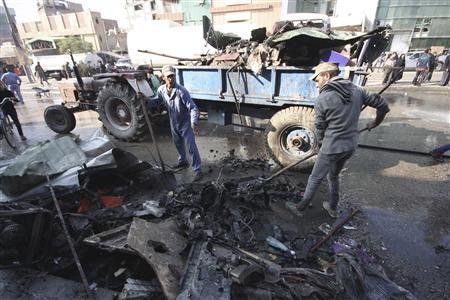 Municipality workers clean debris at the site of a bomb attack in Kerbala, 80 km (50 miles) southwest of Baghdad, November 29, 2012. A car bomb near a bus terminal where Shi'ite pilgrims usually gather killed another two people, a spokesman for the local health office said. REUTERS/Mushtaq Muhammed