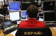 Las rentabilidades de la deuda española a italiana ampliaban sus recientes descensos el jueves por el alivio de que el riesgo inmediato relacionado con Grecia haya disminuido, generando confianza en los inversores para hacerse con deuda de la periferia de la zona euro. En la imagen, un operador mira las pantallas en una subasta de bonos en Madrid, el 8 de noviembre de 2012. REUTERS/Andrea Comas