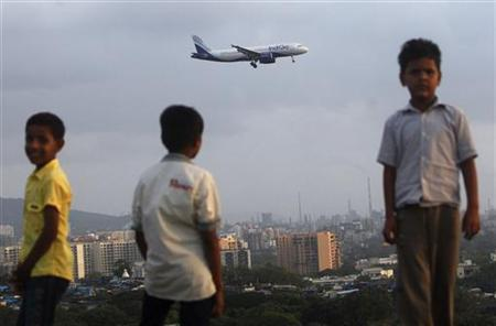 Children stand on top of a hill overlooking Chhatrapati Shivaji International Airport as an Airbus A320 aircraft of comes in to land in Mumbai September 17, 2012. REUTERS/Vivek Prakash/Files