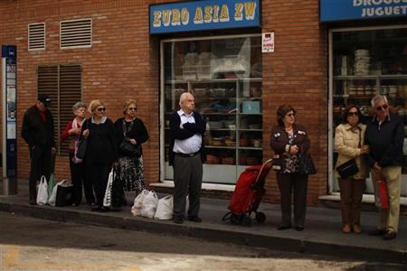 People wait at a bus stop in front of an Asian shop after shopping in downtown Malaga, southern Spain May 4, 2012. REUTERS/Jon Nazca