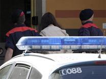 """Un total de 200 jueces españoles han firmado un documento contra el indulto concedido la semana pasada por el Gobierno a cuatro policías condenados por torturas, alegando que la decisión """"dinamita"""" la separación de poderes. En esta imagen de archivo, dos Mossos d'Esquadra escoltan a una detenida en Gerona, el 21 de mayo de 2010. REUTERS/Stringer"""