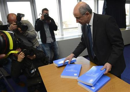 Lord Justice Leveson (R) poses for photographs with his report into the culture, practice and ethics of the press in London November 29, 2012. REUTERS/Paul Hackett