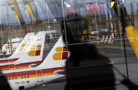 Spanish airline Iberia planes parked on the tarmac are reflected on a window as a passenger walks by during a pilot strike at Madrid's Barajas airport December 18, 2011. REUTERS/Susana Vera