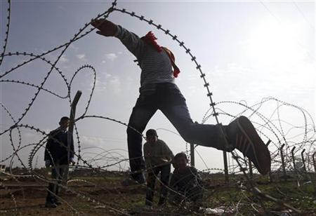 Syrian boys from the northern Syrian town of Ras al-Ain attempt to cross the border back into Syria at the Turkish border town of Ceylanpinar, Sanliurfa province, November 24, 2012. REUTERS/Amr Abdallah Dalsh