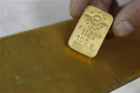 An employee from Bulgaria's largest zinc and lead smelter, KCM, displays a 100 g gold plate and a 13 kg gold bullion near the city of Plovdiv October 20, 2011. REUTERS/Stoyan Nenov/Files