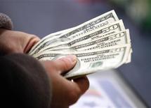 Покупатель считает деньги у кассы в магазине Toys R Us store в День благодарения в Манчестере, Нью-Гемпшир 22 ноября 2012 года. Экономика США росла в третьем квартале быстрее, чем предполагалось ранее, но эти темпы вряд ли сохранятся надолго, так как нация готовится к резкому сокращению государственных расходов и повышению налогов в следующем году. REUTERS/Jessica Rinaldi