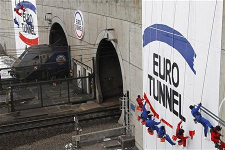 Workers are suspended from ropes as they paint the Eurotunnel logo at the entrance of the channel tunnel in Coquelles December 1, 2010 as Eurotunnel celebrates the 20th anniversary of the Channel Tunnel breakthrough. REUTERS/Pascal Rossignol