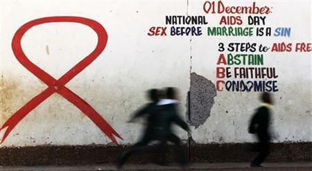 Children run past a mural painting of an Aids ribbon at a school in Khutsong Township, 74 km (46 miles) west of Johannesburg, August 22, 2011. REUTERS/Siphiwe Sibeko/Files