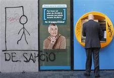 La moratoria de dos años para desalojos de familias desahuciadas en España aprobada por el Gobierno este mes debilita ligeramente la posición financiera de los bancos en el mercado hipotecario nacional, dijo la agencia Moody's en un informe divulgado el jueves. Imagen del 19 de noviembre de un cajero de una caja con una pintada contra los desahucios en el centro de Madrid. REUTERS/Juan Medina
