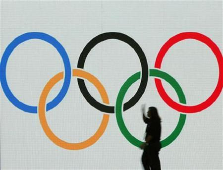 A worker prepares a stage with a display of the Olympic rings at the Raffles City Convention Centre in Singapore July 5, 2005. MDIAT REUTERS/Bazuki Muhammad/Files