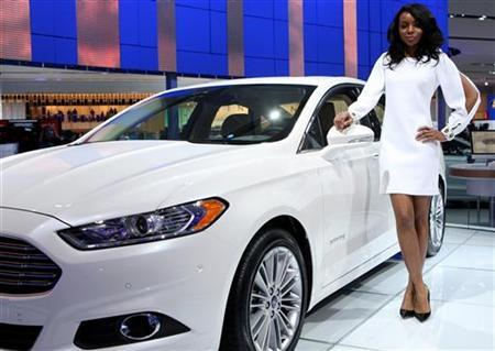 Model Tiffany Moore stands next to a Ford Fusion Hybrid on the final press preview day for the North American International Auto Show in Detroit, Michigan, January 10, 2012. REUTERS/Rebecca Cook