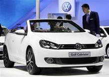 A visitor sitting in a Volkswagen Golf Cabriolet speaks to a staff member at Auto China 2012 in Beijing April 23, 2012. Volkswagen is shifting its expansion in China to the western region where Europe's largest car maker needs more production bases to strengthen its dominance in the world's biggest auto market. REUTERS/Jason Lee (CHINA - Tags: TRANSPORT BUSINESS)