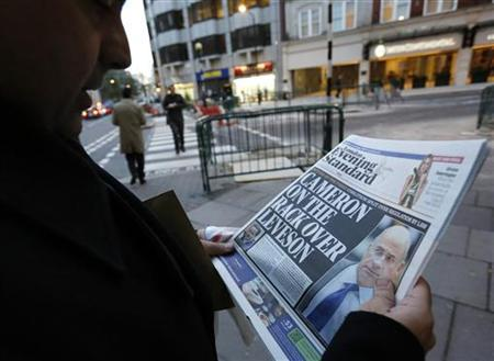 A man reads a newspaper article about Lord Justice Brian Leveson's report on media practices in central London November 29, 2012. British Prime Minister David Cameron said on Thursday that he had serious concerns about legislation to regulate the media, risking a split in his coalition after a damning inquiry triggered by a phone-hacking scandal proposed a press watchdog backed in law. REUTERS/Olivia Harris