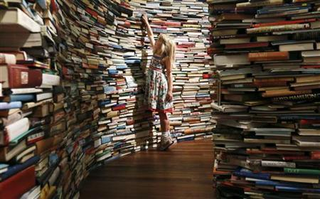 Leona, 7, poses inside a labyrinth installation made up of 250,000 books titled ''aMAZEme'' by Marcos Saboya and Gualter Pupo at the Royal Festival Hall in central London July 31, 2012. REUTERS/Olivia Harris/Files