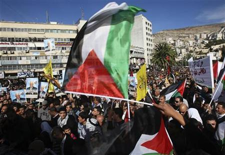 People wave Palestinian flags during a rally in the West Bank city of Nablus, supporting the resolution that would change the Palestinian Authority's United Nations observer status from 'entity' to 'non-member state' November 29, 2012. REUTERS/Abed Omar Qusini
