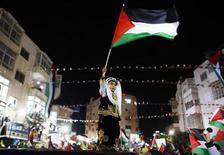 """La Asamblea General de la ONU, compuesta por 193 países, aprobó mayoritariamente el jueves una resolución que mejora el estatuto de observador de la Autoridad Palestina, pasando de """"entidad"""" a miembro no estado, lo que supone un reconocimiento implícito de un estado palestino. En la imagen del 29 de noviembre, un niño palestino con un traje tradicional ondea una bandera palestina en una manifestación en la ciudad cisjordana de Ramala tras la votación. REUTERS/Marko Djurica"""