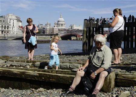 People walk by the River Thames on the South Bank during a warm day in London September 8, 2012. Saint Paul's Cathedral can be seen in the background. REUTERS/Kevin Coombs