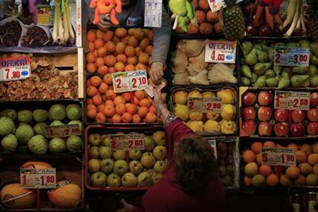 A woman takes a note from a greengrocer's assistant at the Pino Montano market in the Andalusian capital of Seville November 28, 2012. REUTERS/Marcelo del Pozo/Files