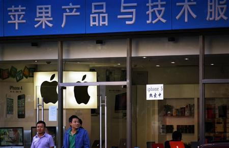 Customers walk out of a store selling and advertising Apple products, including both the iPhone 4 and iPhone 5, in central Beijing September 28, 2012. REUTERS/David Gray
