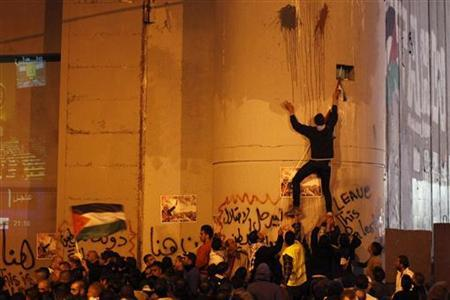Palestinians take part in a rally as another climbs on Israel's controversial barrier in the West Bank city of Bethlehem November 29, 2012. REUTERS/ Ammar Awad