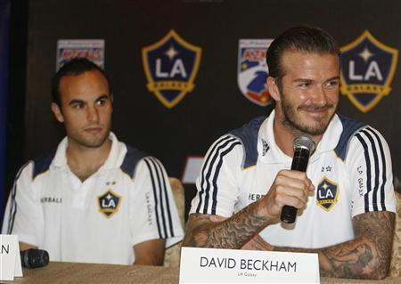 Los Angeles Galaxy's David Beckham (R) answers media queries while his teammate Landon Donovan watches during a news conference in Manila December 1, 2011. REUTERS/Cheryl Ravelo