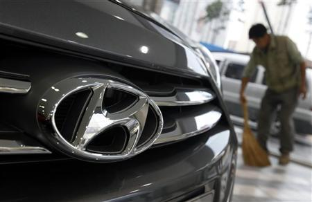 The logo of Hyundai Motor is seen on the on a car as a worker sweeps a floor at a Hyundai dealership in Seoul October 25, 2012. REUTERS/Kim Hong-Ji