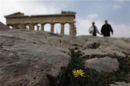 A couple walks in front of the Parthenon temple at the Acropolis hill in Athens November 27, 2012. A bleary-eyed Greek Prime Minister Antonis Samaras welcomed on Tuesday an agreement by international lenders to help cut his country's debt and unblock bailout money to avert bankruptcy. REUTERS/John Kolesidis (GREECE - Tags: POLITICS BUSINESS TRAVEL TPX IMAGES OF THE DAY)