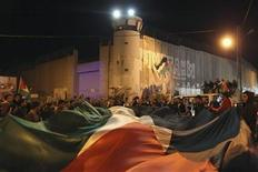 "Palestinians hold a giant flag during a rally in front of Israel's controversial barrier in the West Bank city of Bethlehem November 29, 2012. The 193-nation U.N. General Assembly overwhelmingly approved a resolution on Thursday to upgrade the Palestinian Authority's observer status at the United Nations from ""entity"" to ""non-member state,"" implicitly recognizing a Palestinian state. REUTERS/Ammar Awad (WEST BANK - Tags: POLITICS CIVIL UNREST TPX IMAGES OF THE DAY)"