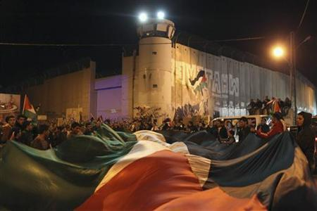 Palestinians hold a giant flag during a rally in front of Israel's controversial barrier in the West Bank city of Bethlehem November 29, 2012. The 193-nation U.N. General Assembly overwhelmingly approved a resolution on Thursday to upgrade the Palestinian Authority's observer status at the United Nations from ''entity'' to ''non-member state,'' implicitly recognizing a Palestinian state. REUTERS/Ammar Awad (WEST BANK - Tags: POLITICS CIVIL UNREST TPX IMAGES OF THE DAY)
