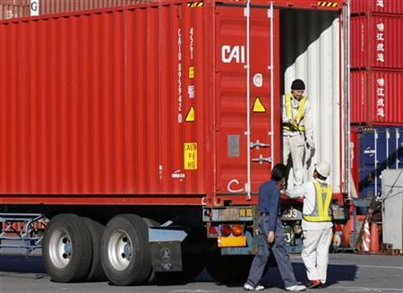 People work next to a container loaded on a truck at a container area at a port in Tokyo November 21, 2012. Japan's exports fell in annual terms for a fifth month in October, hurt by the fallout from a diplomatic row with China and feeble global demand, a further sign the economy may be slipping into recession and adding weight to calls for policy easing. REUTERS/Issei Kato (JAPAN - Tags: BUSINESS POLITICS)