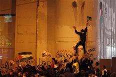 """La Asamblea General de Naciones Unidas, de 193 países, reconoció implícitamente el jueves por una abrumadora mayoría un Estado soberano de Palestina después que el presidente Mahmud Abas pidió al organismo mundial que emitiera un largamente esperado """"certificado de nacimiento"""". En la imagen, palestinos toman parte en una manifestación mientras otro escala por el muro israelí de la controversía en la ciudad cisjordana de Belén, el 29 de noviembre de 2012. REUTERS/ Ammar Awad"""