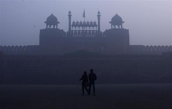 A couple walks in front of the historic Red Fort amid dense fog on a cold winter morning in the old quarters of Delhi January 3, 2012. REUTERS/Adnan Abidi/Files