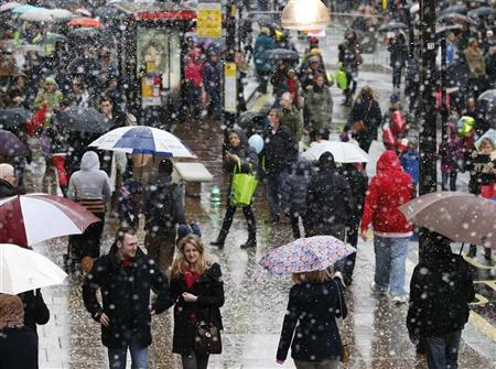 Shoppers walk through fake snow on Oxford Street during a traffic-free pre-Christmas shopping day in central London November 24, 2012. REUTERS/Olivia Harris