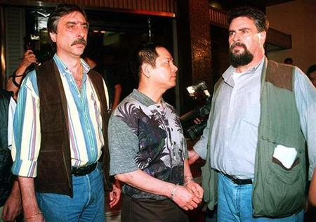 One of the most powerful Chinese Mafia leaders in Asia, Wan Kuok-Koi (C) alias Broken Tooth Koi, is handcuffed after he was arrested by Macau's top crime-fighter, Judicial Police Director Antonio Marques Baptista (R) during an anti-crime raid May 1, 1998. REUTERS/Str Old/Files