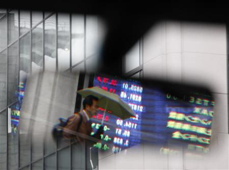 A man passing an electronic board displaying share prices is reflected in a rearview mirror of a taxi in Tokyo April 16, 2010. REUTERS/Yuriko Nakao/Files