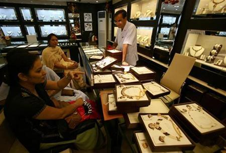 Women sit inside a jewellery shop in Jammu August 3, 2007. REUTERS/Amit Gupta/Files
